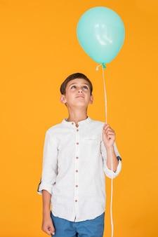 Kleiner junge, der einen blauen ballon betrachtet
