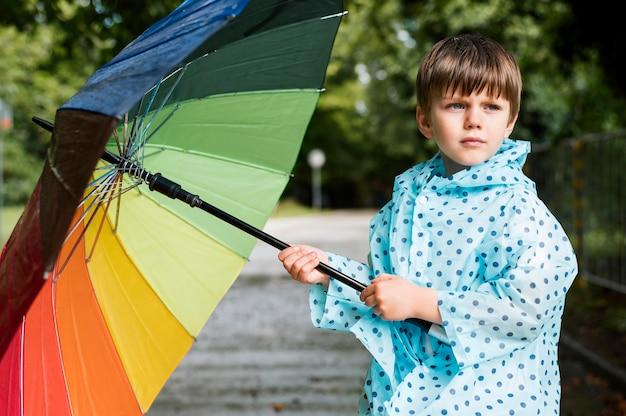 Kleiner junge, der einen bunten regenschirm hält