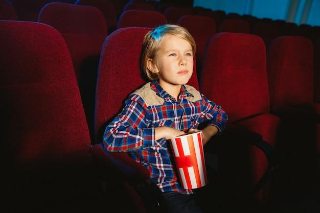 Kleiner junge, der einen film in einem kino, haus oder kino sieht.