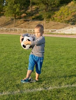 Kleiner junge, der einen fußball auf einem grasbewachsenen sportplatz hält, der in abendsonne schaut
