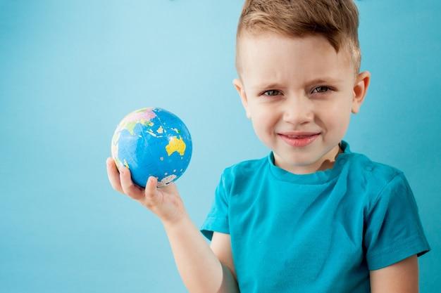 Kleiner junge, der einen globus auf blauem hintergrund hält.