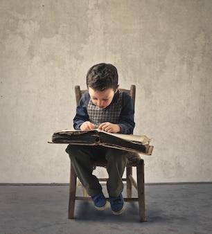 Kleiner junge, der einen kodex liest