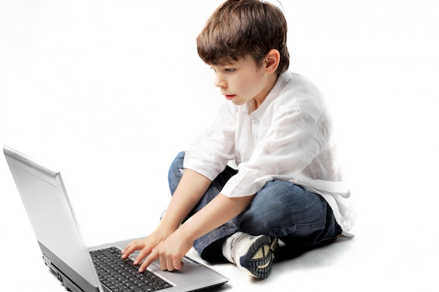 Kleiner junge, der einen laptop verwendet