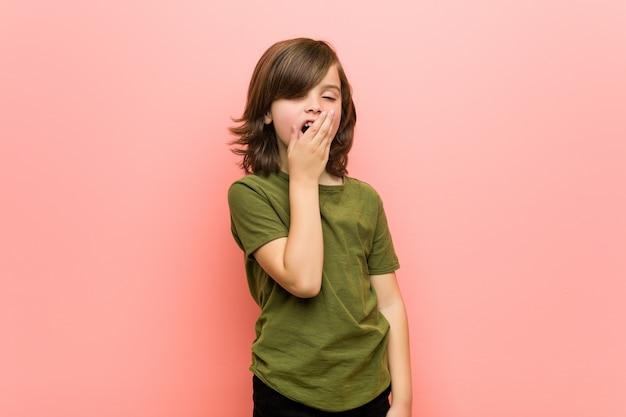 Kleiner junge, der einen müden gestenbedeckungsmund mit der hand zeigend gähnt