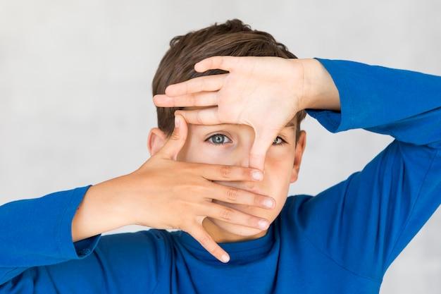 Kleiner junge, der einen rahmen mit seinen fingern macht
