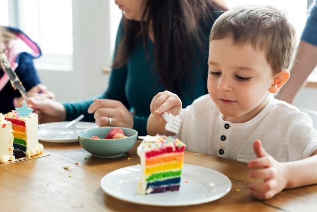 Kleiner junge, der einen regenbogen farbigen kuchen isst