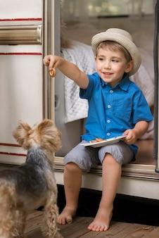 Kleiner junge, der einen teller neben einem niedlichen hund hält