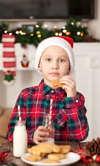 Kleiner junge, der einen weihnachtsplätzchen hält und milch trinkt.