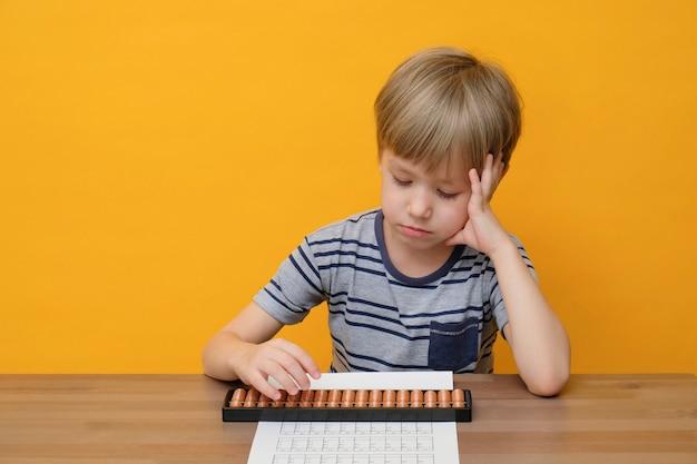 Kleiner junge, der einfache mathematikübungen mit abakuswerten macht.