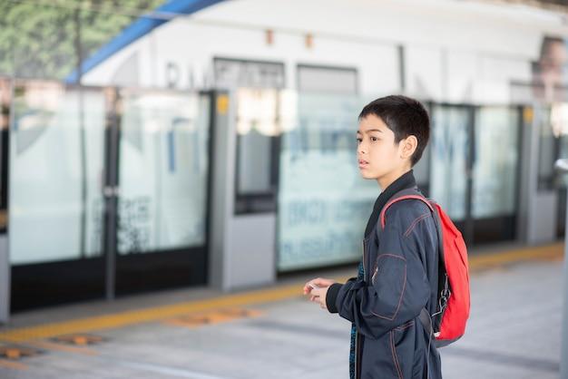 Kleiner junge, der elektrische karte kauft und in die bahnstation des allgemeinen himmels mit familie geht