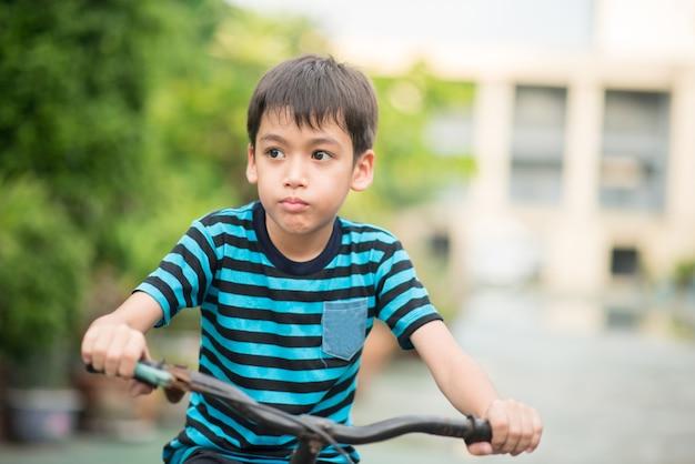 Kleiner junge, der fahrrad auf der straße um das haus reitet