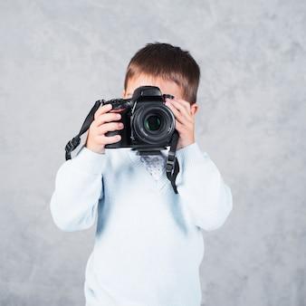 Kleiner junge, der foto mit kamera macht