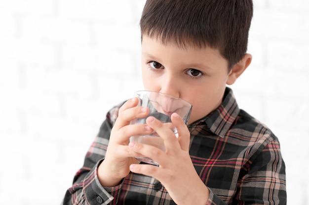 Kleiner junge, der frisches wasser auf licht trinkt Premium Fotos
