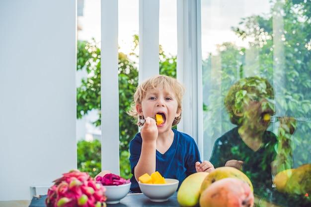 Kleiner junge, der früchte auf der terrasse isst