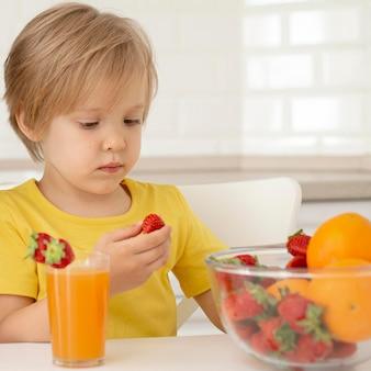 Kleiner junge, der früchte isst