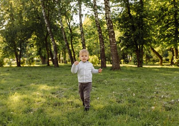 Kleiner junge, der fußball draußen spielt
