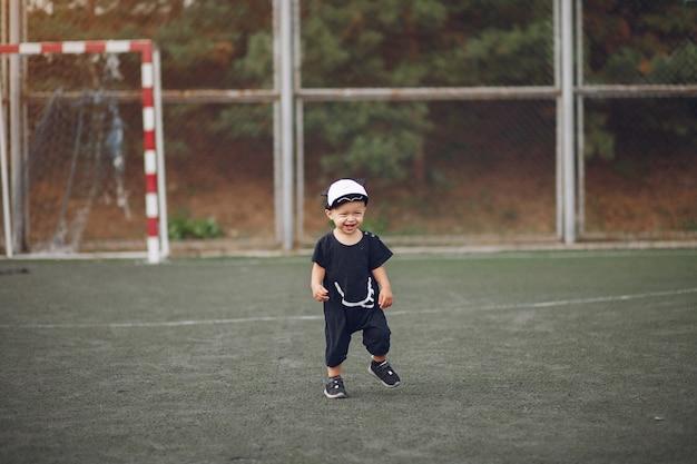 Kleiner junge, der fußball in einem sportplatz spielt