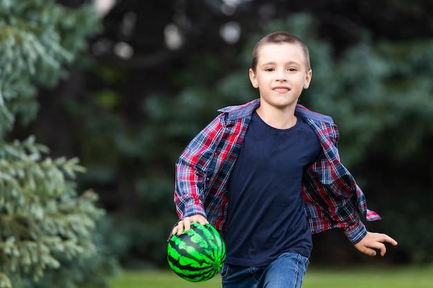 Kleiner junge, der fußball mit fußball auf feld im sommerpark spielt.