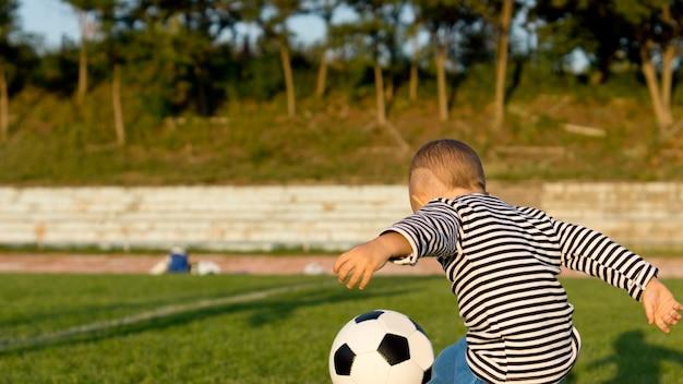 Kleiner junge, der fußball spielt oder fußball, der einen ball tritt