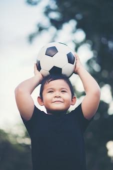Kleiner junge, der fußballfußball spielt