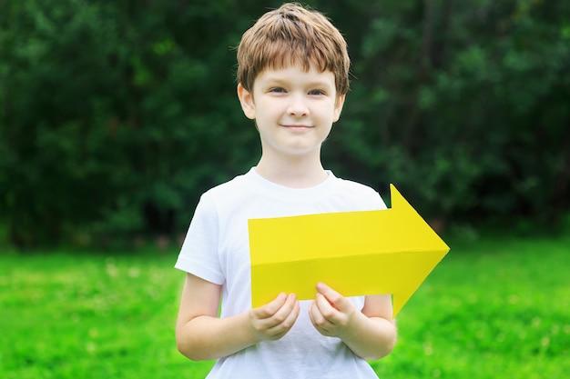 Kleiner junge, der gelben pfeil im sommerpark hält.
