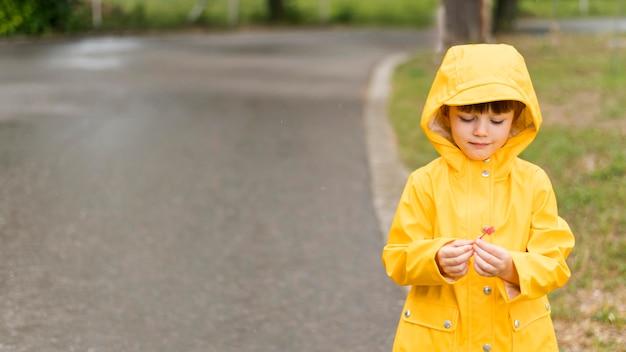 Kleiner junge, der gelben regenmantel mit kopienraum trägt