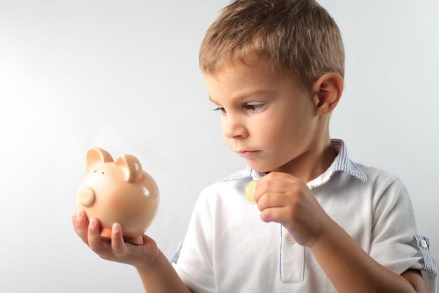 Kleiner junge, der geld spart
