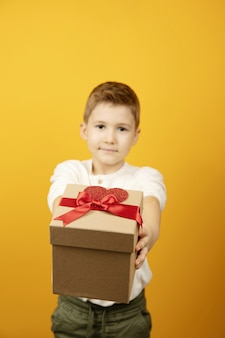 Kleiner junge, der geschenkbox mit rotem band und herzform lokalisiert, kind gibt geschenk. selektiver fokus, fokus auf die geschenkbox, unscharfer hintergrund.