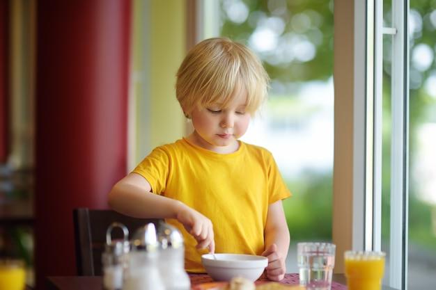 Kleiner junge, der gesundes frühstück im hotelrestaurant isst