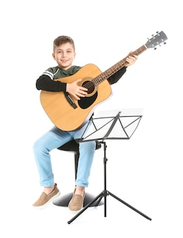 Kleiner junge, der gitarre auf weißer oberfläche spielt