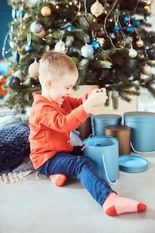 Kleiner junge, der glücklich weihnachtsgeschenke auspackt