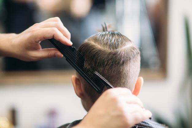 Kleiner junge, der haarschnitt durch friseur beim sitzen im stuhl am barbershop erhält.