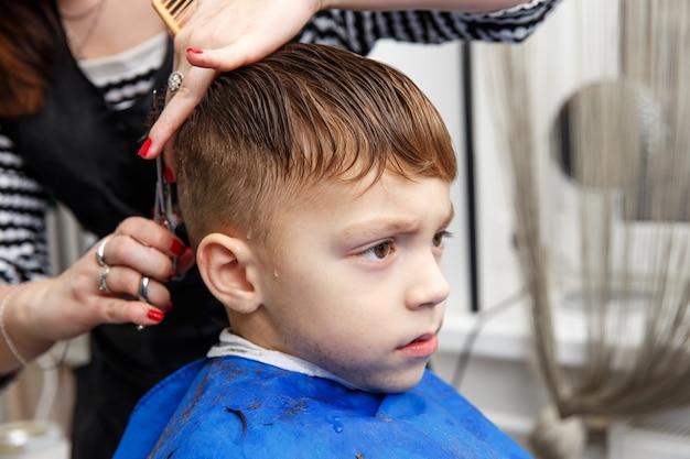 Kleiner junge, der haarschnitt erhält