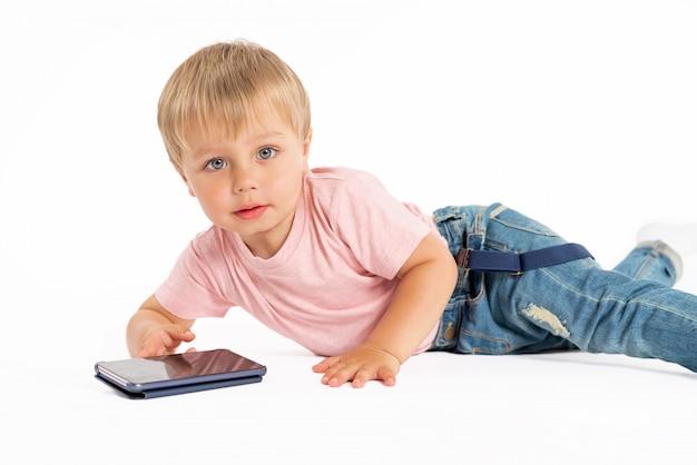 Kleiner junge, der handy verwendet. kind spielt auf dem smartphone. technologie, mobile apps, kinder- und elternberatung, lifestyle