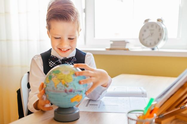 Kleiner junge, der hauptarbeit über studientabelle mit einer kugel und einem arbeitsbuch studiert oder abschließt
