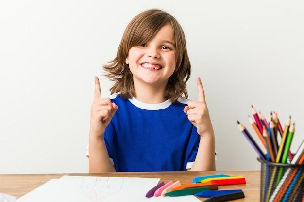 Kleiner junge, der hausarbeit auf seinem schreibtisch zeigt oberseite malt und tut.
