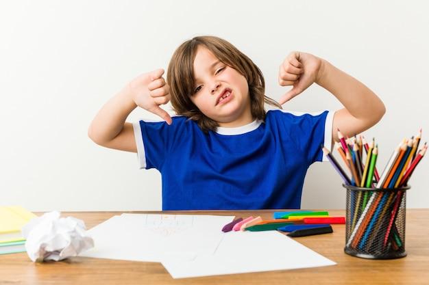 Kleiner junge, der hausaufgaben auf seinem schreibtisch unten zeigt daumen malt und tut und abneigung ausdrückt.