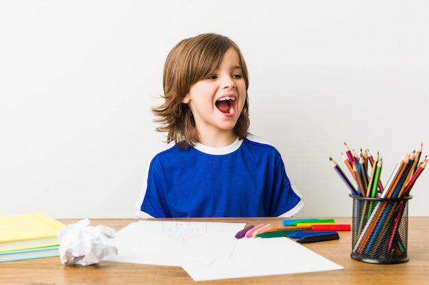 Kleiner junge, der hausaufgaben auf seinem schreibtischschreien malt und tut.