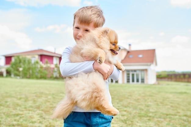 Kleiner junge, der haustierhund hält