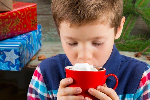 Kleiner junge, der heiße schokolade mit marshmallows auf dem hintergrund von geschenken, weihnachtsbaum und weihnachtsdekorationen trinkt