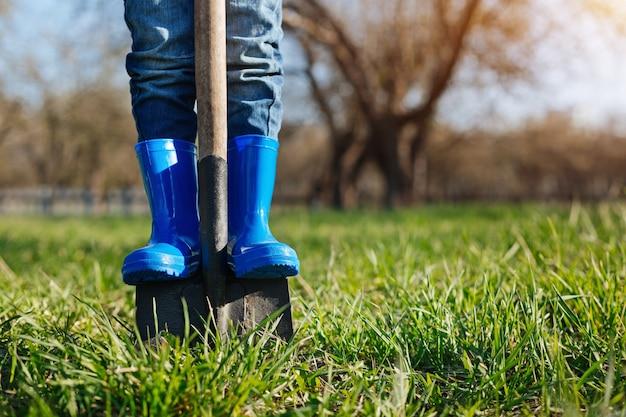 Kleiner junge, der hellblaue gummistiefel trägt, hilft seinen familienmitgliedern, indem er einen spaten in den boden gräbt