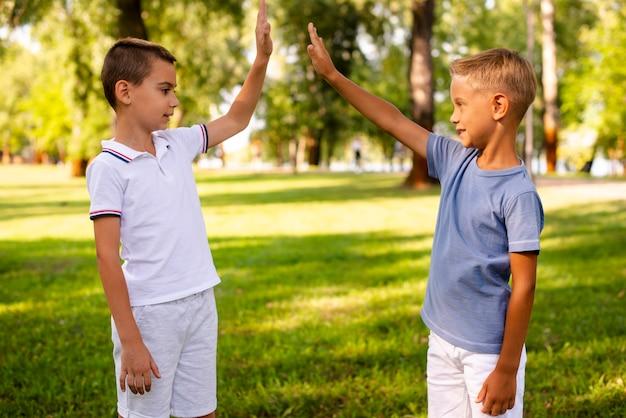 Kleiner junge, der hoch im park fiving ist