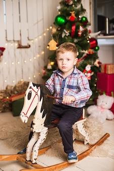 Kleiner junge, der hölzernes schaukelpferd vor weihnachtsbaum reitet