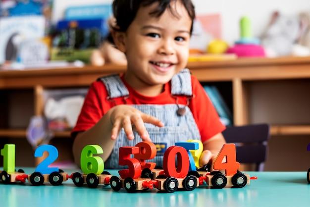 Kleiner junge, der hölzernes spielzeug der mathematik an der kindertagesstätte spielt