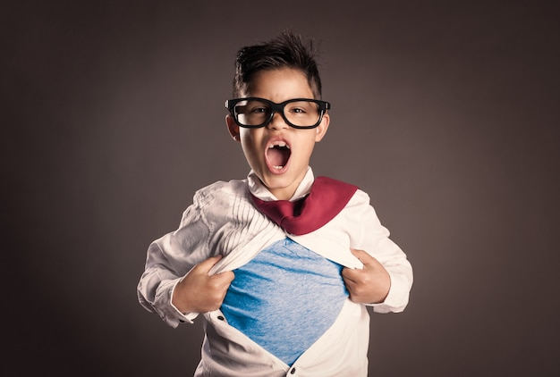Kleiner junge, der ihr hemd wie ein superheld auf einem grau öffnet