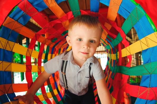 Kleiner junge, der im farblabyrinth spielt. spielplatz im innenbereich für kinder.