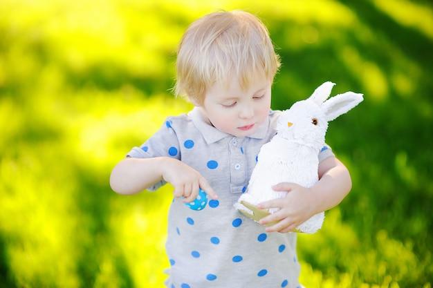 Kleiner junge, der im frühjahr für garten ostereies am ostertag jagt. nettes kleines kind mit traditionellem häschen fest feiernd