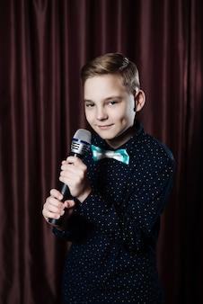 Kleiner junge, der im mikrofon singt.