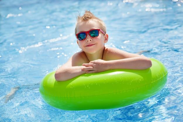 Kleiner junge, der im pool mit großem hellgrünem gummiring schwimmt