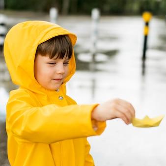 Kleiner junge, der im regen mit einem papierboot spielt